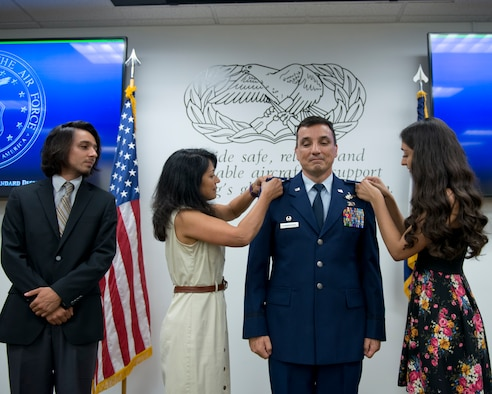 Lt. Col. Christian Cunningham, 167th Maintenance Commander, was promoted to the rank of Colonel during a ceremony at the Martinsburg, W.Va. air base, Aug 6.  Pinning Col. Cunningham was his wife Narmada, his daughter Asha, his son Iain looks on. (U.S. National Guard photo by Tech. Sgt. Michael Dickson)