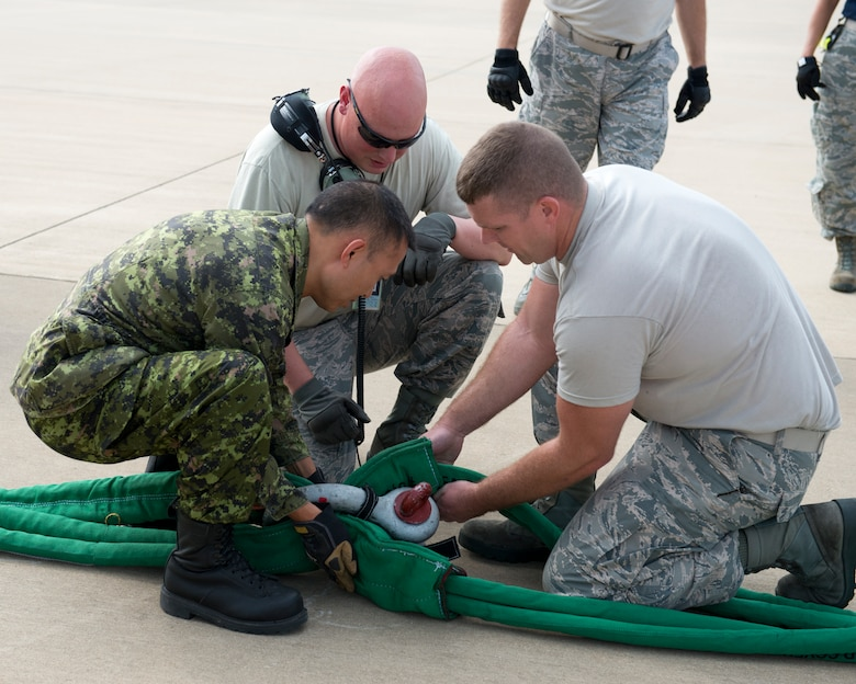 Members of the 167th Maintenance Squadron and the Royal Canadian Air Force assemble a tow rope that connects ground equipment to a C-17 Globemaster III aircraft during a Crashed, Damaged or Disabled Aircraft Recovery training event at the 167th Airlift Wing, Aug 6. Canadian maintainers travelled to the 167th to gain experience on the new crash kit along with members of several other U.S. Air Force units. (U.S. National Guard photo by Tech. Sgt. Michael Dickson)