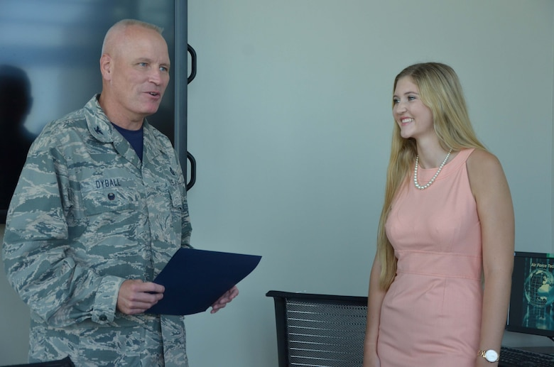 Col. Jeffrey W. Dyball, vice commander of the Air Force Technical Applications Center, Patrick AFB, Fla., presents a certification of recognition to Madison Zook, recipient of AFTAC Company Grade Officer Council's annual scholarship.  Zook, a recent Edgewood Jr./Sr. High School graduate, received the $500 award July 29, 2016 for her essay on business analytics.  (U.S. Air Force photo by Susan A. Romano)