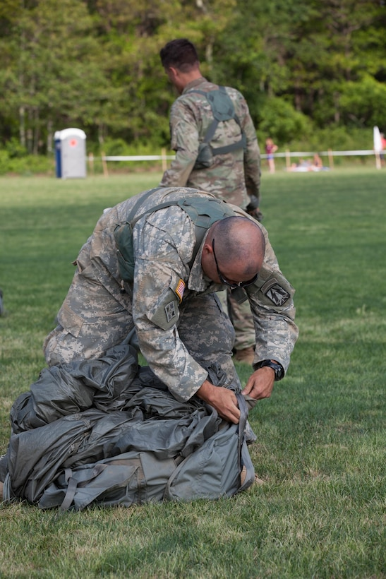 U.S. Army Reserve Paratrooper Staff Sgt. Edward Reagan, 982nd Combat Camera Company (Airborne), puts his parachute into a Universal Parachutist Kit Bag during Leapfest 2016 in West Kingston, R.I., August 4, 2016. Leapfest is an International parachute training event and competition hosted by the 56th Troop Command, Rhode Island Army National Guard to promote high level technical training and esprit de corps within the International Airborne community. (U.S. Army photo by Sgt. Brady Pritchett / Released)