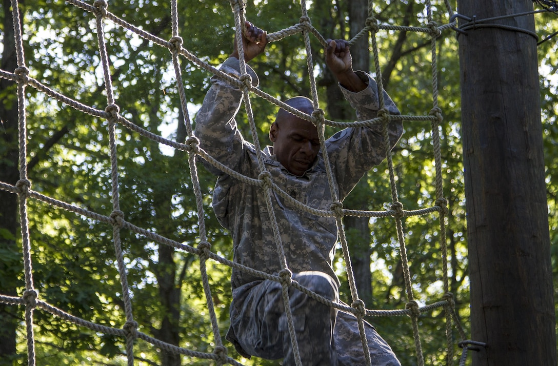 Task Force Wolf instructor, Army Reserve Sgt. 1st Class Harry Bowles from the 2nd of the 399th Training Support Battalion (ROTC), demonstrates the correct way to master The Tough One for the Cadet Initial Entry Training (CIET) candidates on the confidence course during U.S. Army ROTC Cadet Summer Training (CST16), at Ft Knox, Ky., June 8. (U.S. Army Reserve photo by Sgt. Karen Sampson/ Released).