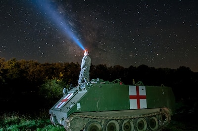 Army Staff Sgt. Brad Foster, a combat medic with the Oregon Army National Guard's Headquarters and Headquarters Company, 3rd Battalion, 116th Heavy Brigade Combat Team from Pendleton, Ore., looks up at the night sky from the top of an M113 medical evacuation vehicle during Exercise Saber Guardian 16 at the Romanian Land Forces Combat Training Center in Cincu, Romania, Aug. 3, 2016. Army photo by Spc. Timothy Jackson