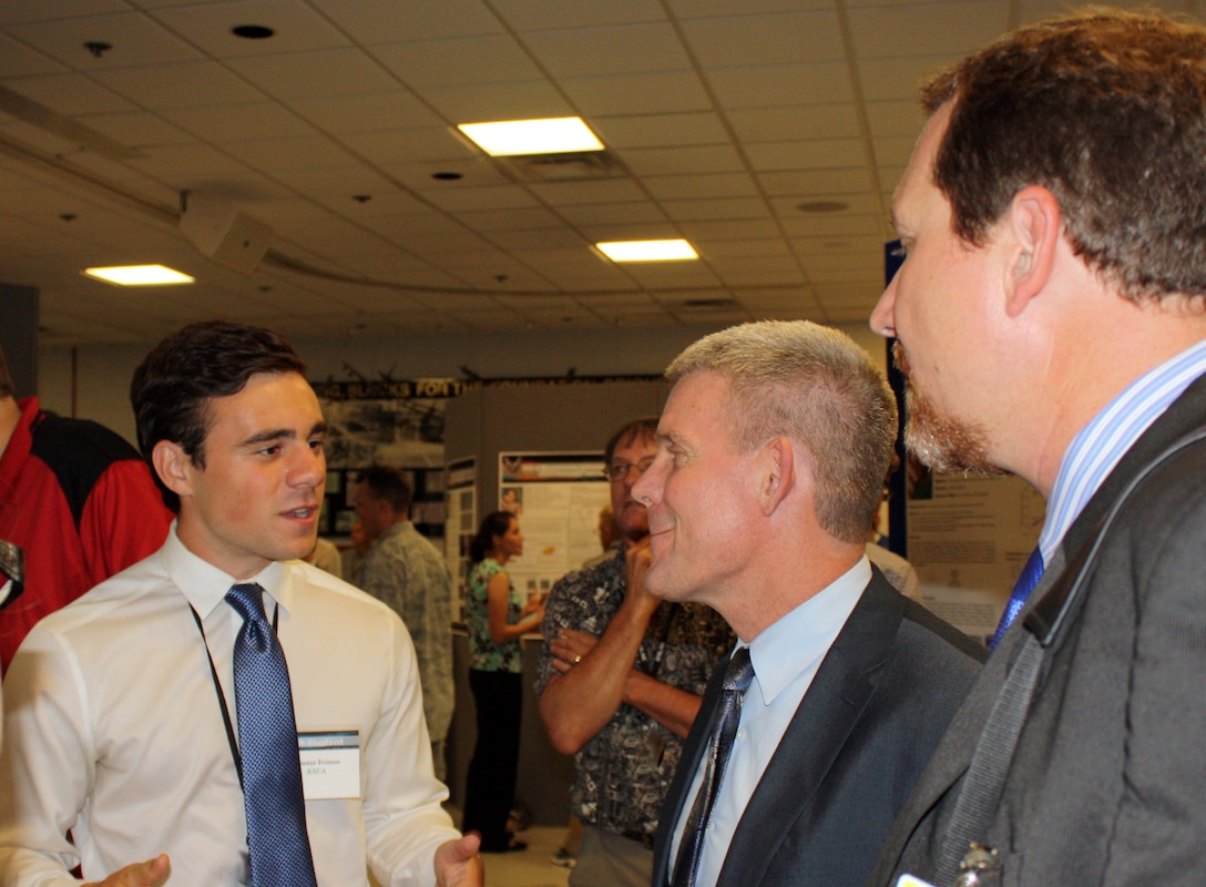Thomas Lockhart (center), Director, AFRL Materials and Manufacturing Directorate, and Chad Watchorn (right), Executive Director, Regional STEM Collaborative, speak with interns Connor Eviston and Megan Imel (unpictured), undergraduate students from the University of Cincinnati and Wright State University, respectively, during the 2016 RX Summer Student Poster Session, Aug. 5. Eviston and Imel researched nondestructive evaluation and thermal signals for impact-damaged polymer matrix composites this summer. (U.S. Air Force photo/Marisa Novobilski)