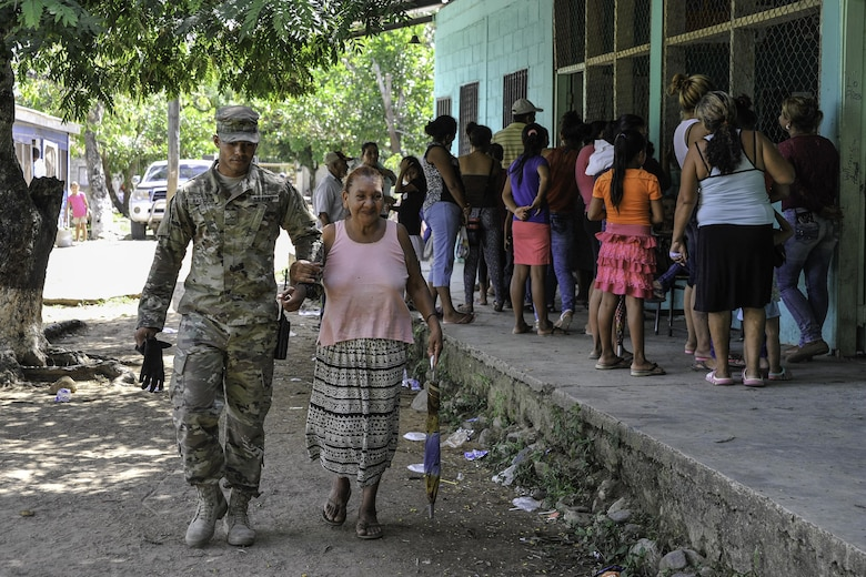 U.S. Army Pvt. Gabriel Hassoun, Joint Task Force-Bravo Army Forces, walks with an elderly woman during a Medical Readiness Training Exercise operation in Trujillo, Honduras, July 29, 2016. While MEDRETEs greatly help the local populations where they are conducted, the service members executing the operations also receive valuable medical training and experience that comes from operating in remote and/or austere environments. (U.S. Air Force photo by Staff Sgt. Siuta B. Ika)