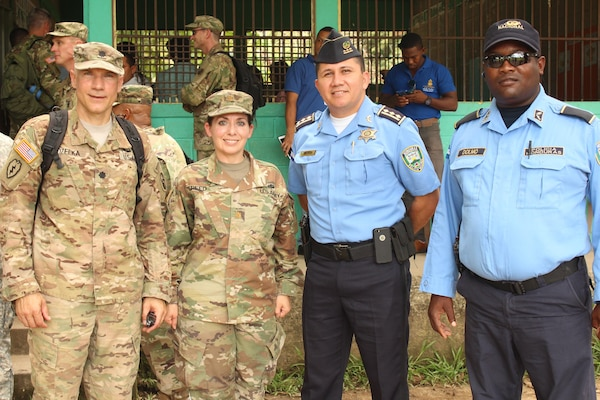 U.S. Army Lt. Col. Glenn Kozelka (far left), operations director for Joint Task Force-Bravo, and U.S. Army Major Rosemary Reed (left), Civil Military Operations deputy director for JTF-Bravo, pose for a photo with two Honduran Police Officers during a Medical Readiness Training Exercise in the village of La Boveda, Trujillo, July 29, 2016. A total of 1,072 patients of all ages received treatment during the two-day event that involved key leaders from both JTF-Bravo and Honduras. (U.S. Army photo by Maria Pinel)