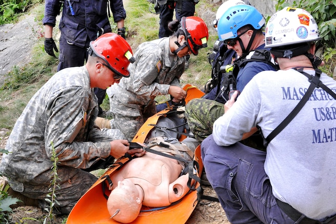 Army Spc. Alex Buckley, left, and Army Pfc. Geraldine Jimenez work with civilian search and rescue teams to secure a simulated casualty during Vigilant Guard 2016 at Camp Ethan Allen Training Site, Jericho, Vt., July 30, 2016. Buckley is a wheeled vehicle mechanic assigned to the Massachusetts National Guard's 181st Engineer Battalion. Jimenez is a truck driver assigned to the Massachusetts National Guard's Forward Support Company, 101st Engineers. The National Guard and U.S. Northern Command sponsor the emergency response exercise, which provides an opportunity for service members to improve cooperation with civilian, military and federal partners as they prepare for emergencies and catastrophic events. Army National Guard photo by Staff Sgt. Ashley Hayes