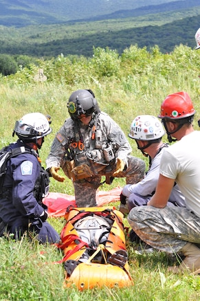 Army Staff Sgt. Stephen Trala, center, talks with civilian search and rescue teams and soldiers during a search-and-rescue exercise as part of Vigilant Guard 2016 at Camp Ethan Allen Training Site, Jericho, Vt., 2016. Trala is a flight medic assigned to Company C, 3rd Battalion, 126th Aviation Regiment Air Ambulance. Army National Guard photo by Staff Sgt. Ashley Hayes