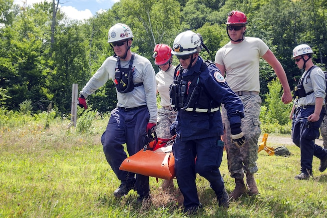 Soldiers, first responders from Federal Emergency Management Agency's urban search-and-rescue team carry a litter with a simulated casualty to a medevac site during Vigilant Guard 2016 at Camp Ethan Allen Training Site, Jericho, Vt., July 29, 2016. Army National Guard photo by Spc. Avery Cunningham