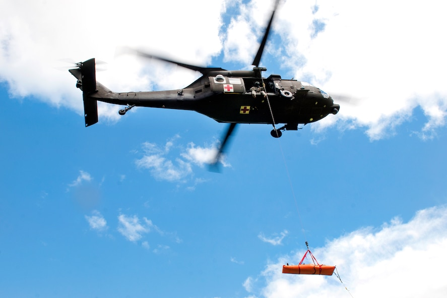 An HH-60M Black Hawk helicopter crew hoists a simulated casualty.