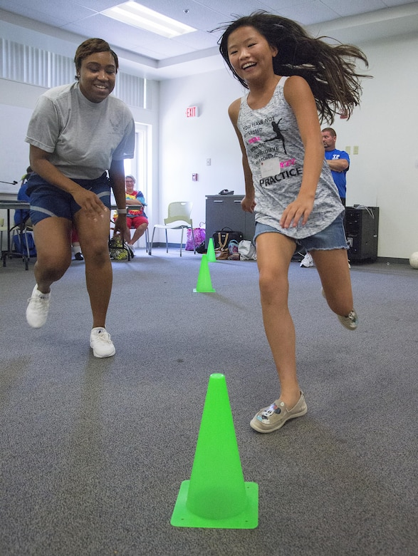 Hannah Haley, 11, and Airman 1st Class Whitney Parker, 88th Medical Operations Squadron administrative technician, race from cone-to-cone in a game at Stop Bullying, Give Peace a Chance, an anti-bullying event in the Wright-Patterson Air Force Base, Ohio, Religious Education Facility Aug. 2, 2016. Haley, the daughter of Dan and Renea Haley, 88th Medical Support Squadron health systems specialist, is starting the sixth-grade at Northwestern Elementary School in Clark County, Ohio. (U.S. Air Force photo/R.J. Oriez)