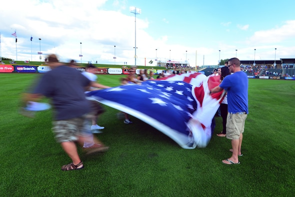 A giant-sized United States flag is unfurled in centerfield of Werner Park in Papillion, Neb. on Aug. 7 as part of a special military appreciation night. Werner Park is located near Offutt Air Force Base, Nebraska which employs more than 8,000 active-duty and civilian employees.  (U.S. Air Force photo by Josh Plueger)