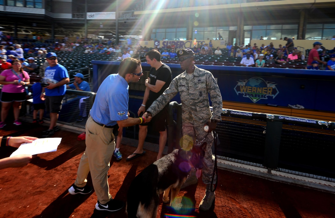 U.S. Air Force Staff Sgt. Elbert Foreman Jr., a military working dog handler, meets with staff members of the Omaha Storm Chasers baseball team during a military appreciation game held at Werner Park, Papillion, Neb. on Aug. 7.  Foreman and his dog Rocky ceremoniously place the game ball on the mound for the evening's game.  (U.S. Air Force photo by Josh Plueger)