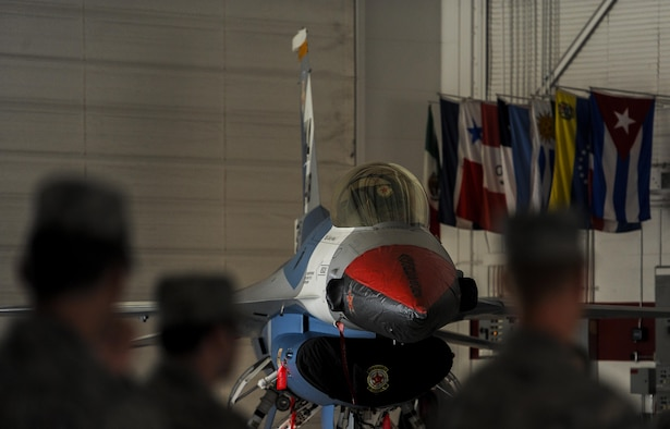 "An F-16 Fighting Falcon, assigned to the 64th Aggressor Squadron, with the new ""splinter"" paint scheme sits in the U.S. Air Force Thunderbird hangar at Nellis Air Force Base, Nev., during the 57th Adversary Tactics Group change of command ceremony Aug. 5, 2016. The new paint scheme for the F-16 will serve as the closest representation of real world threats for pilots who train at Nellis AFB. (U.S. Air Force photo by Airman 1st Class Kevin Tanenbaum/Released)"