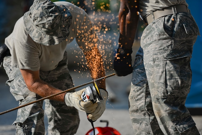 U.S. Air Force Senior Master Sgt. Todd Butcher, New Jersey Air National Guard civil engineer, uses an angle grinder with an abrasive disc to cut a reinforcing bar held by Master Sgt. Delroy Wallace in Vau i Dejës, Albania on July 11, 2016. The 177th Fighter Wing civil engineers were working on Humanitarian and Civic Assistance renovation projects at a local medical clinic during their two week long deployment for training. New Jersey and Albania are paired under the National Guard's State Partnership Program and are a proven partnership built upon shared values, experiences and vision. (U.S. Air National Guard photo by Master Sgt. Andrew J. Moseley/Released)