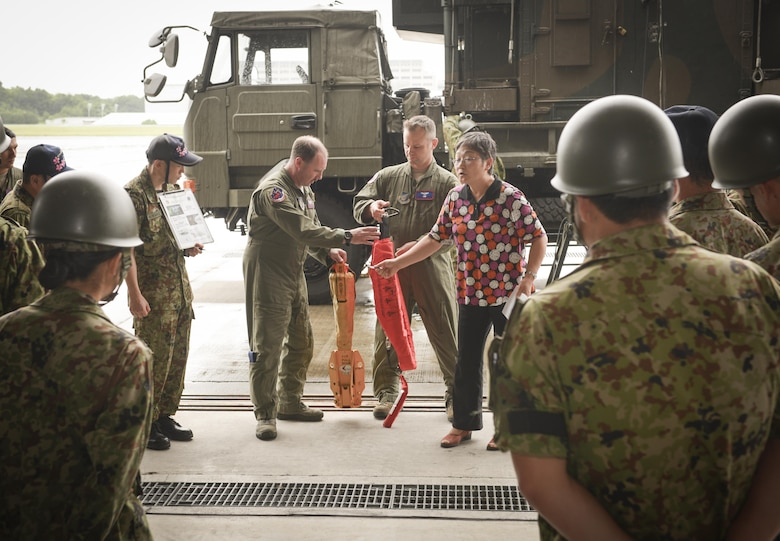 Tech. Sgt. David Jacobs, center left, 459th Airlift Squadron UH-1 Iroquois flight engineer, and Senior Master Sgt. Edward Spondenburg, 459 AS superintendent, demonstrate a forest penetrator to members of the Japan Ground Self-Defense Force with translation from Mitsuru Takahashi, 374th Airlift Wing chief of community relations at Camp Tachikawa, July 26, 2016. The 459 AS demonstrated their search and rescue capabilities, which supports Japan in disaster-response efforts.  (U.S. Air Force photo by Airman 1st Class Elizabeth Baker/Released)