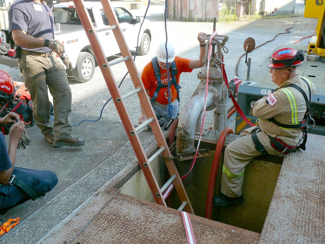 A confined space rescue watch team from Industrial Emergency Services, LLC, and an AEDC pipefitter, stand by for AEDC personnel in a vault and a connecting 48-inch diameter water line. An inspection was performed on the inside of the water line pipe to determine if there is any cause for a larger than normal pressure drop in this section of pipe. The inspection was part of the maintenance performed during a recent 11-day water and power outage. (AEDC photo)