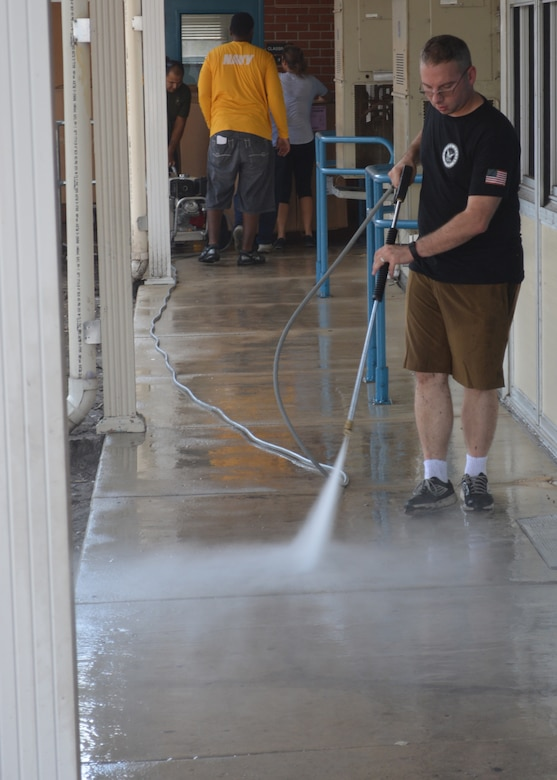 Damage Controlman 1st Class Joshua Stokes power washes a hallway at Oak Hill Academy in Jacksonville, Fla. Stokes, a Sailor with Southeast Regional Maintenance Center in Mayport, volunteered to help clean, assemble furniture and prepare classrooms for pre-K to 5th grade students with moderate to severe autism. SERMC provides surface ship maintenance, modernization and technical expertise in support of the ships of the US Navy. SERMC also provides visiting vessel services to foreign navies. Photo by Scott Curtis
