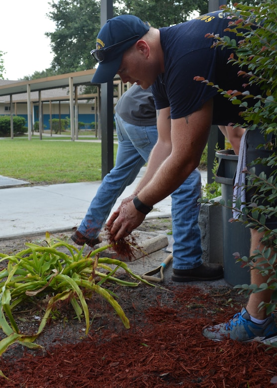 Cryptologic Technician Technical Chief Devin Simpson spreads mulch on the grounds of Oak Hill Academy in Jacksonville, Fla. Simpson, a Sailor with Southeast Regional Maintenance Center (SERMC) in Mayport, Fla., led 20 Sailors who volunteered to help put the finishing touches inside the classrooms and general clean-up around the campus prior to the new student body orientation Aug. 12. Photo by Scott Curtis