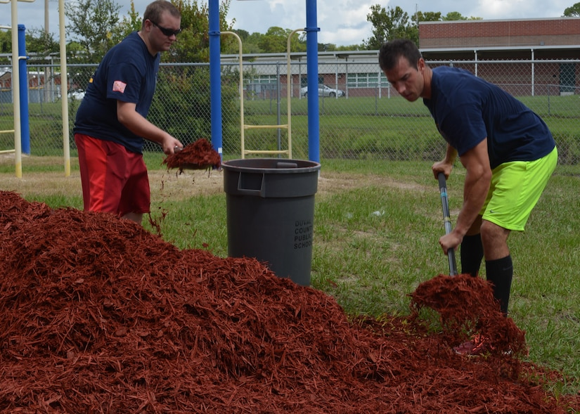 Machinist's Mate 1st Class Brian Hill (R) and Engineman 1st Class Robin Mosely (L) shovel mulch into a makeshift wheel-barrow at Oak Hill Academy in Jacksonville, Fla. Hill and Mosely are Sailors with Southeast Regional Maintenance Center (SERMC) in Mayport, Fla. Both volunteered to help clean, assemble furniture and prepare classrooms for the 2016-2017 school year. SERMC provides surface ship maintenance, modernization and technical expertise in support of the ships of the US Navy. Photo by Scott Curtis