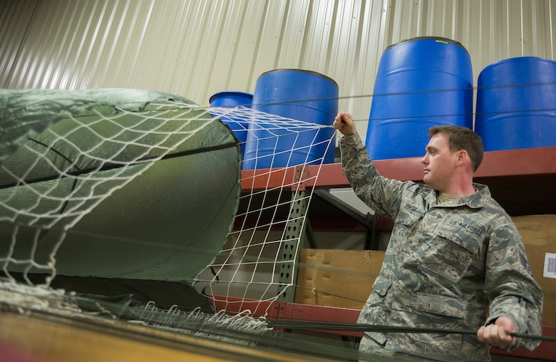 Staff Sgt. Justin Spencer, 919th Special Operations Logistics Readiness Squadron, sets up a parachute at Duke Field, Fla.  The parachutes are attached to 300-pound bundles and loaded onto aircraft so new loadmasters can perform their initial airdrop training and prior-qualified Airmen can maintain proficiency.  (U.S. Air Force photo/Sam King)