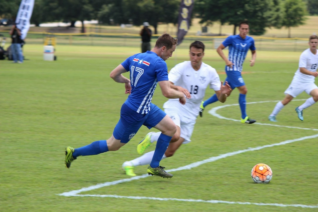 U.S. Air Force 1st Lt. Micah Cummins, number 17, 100th Air Refueling Wing chief of protocol, runs by an All-Navy defender during the finals of the All-Armed Forces Championships May 15, 2016, in Columbus, Georgia. Cummins set up the first goal and scored the second, helping the Air Force defeat the Navy 3-2, bringing home the gold for the Air Force. (Courtesy photo)