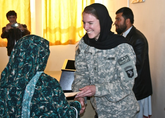 U.S. Air Force 1st Lt. Brittany Martin, right, a public affairs officer with the Laghman Provincial Reconstruction Team, working with 1st Battalion, 133rd Infantry Regiment, Task Force Ironman, which is part of the 2nd Brigade Combat Team, 34th Infantry Division, presents a certificate to an Afghan journalism seminar participant at the Information, Culture and Youth Center in Mehtar Lam, Laghman province, Afghanistan, Feb. 23, 2011. (DoD photo by Staff Sgt. Ryan C. Matson, U.S. Army/Released)