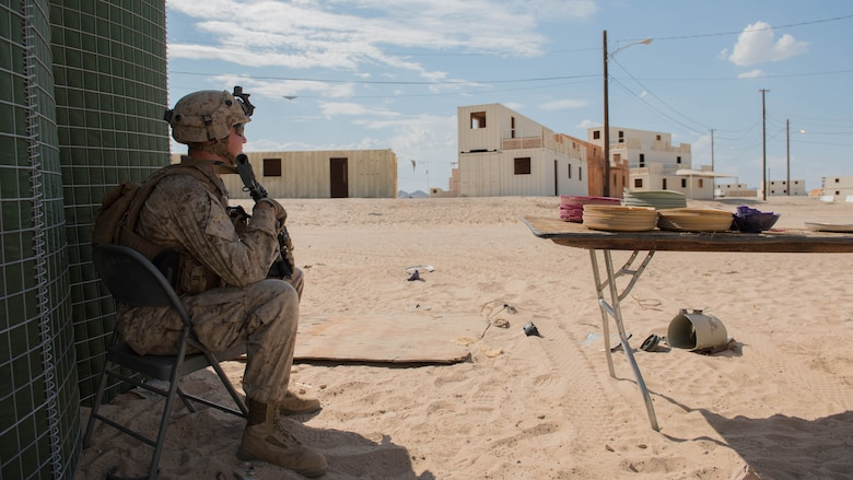 Lance Cpl. Tyler Zaugg, rifleman, Kilo Company, 3rd Battalion, 5th Marine Regiment sits on post outside of a makeshift police station during the Marine Air Ground Task Force Integrated Experiment 2016 at Marine Corps Air Ground Combat Center Twentynine Palms, Calif.  July 29, 2016. The exercise forced Marines to go up against a futuristic oppositional force with access to modern day technology, jamming capabilities, and support from the community.