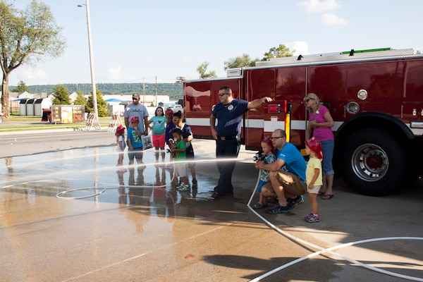 Children challenge each other for accuracy in putting out a fire on a simulated burning building during Defense Distribution Center Susquehanna's National Night Out on Aug. 2.