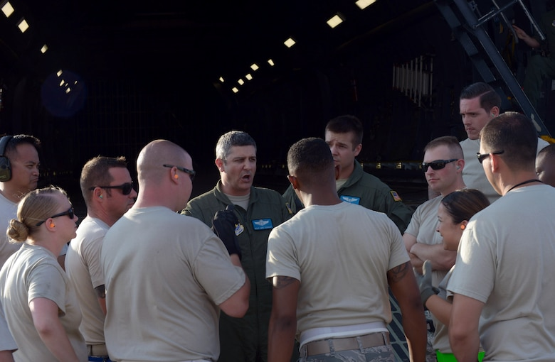 Master Sgt. Jeff Stanley, a load master with the 9th Airlift Squadron at Dover Air Force Base (AFB), Del., provides Airmen a mission safety brief at Ellsworth AFB, S.D., Aug. 2, 2016. Approximately 650 tons of equipment is being transported to Andersen AFB, Guam, in support of the continuous bomber presence mission. (U.S. Air Force photo by Airman Donald Knechtel)