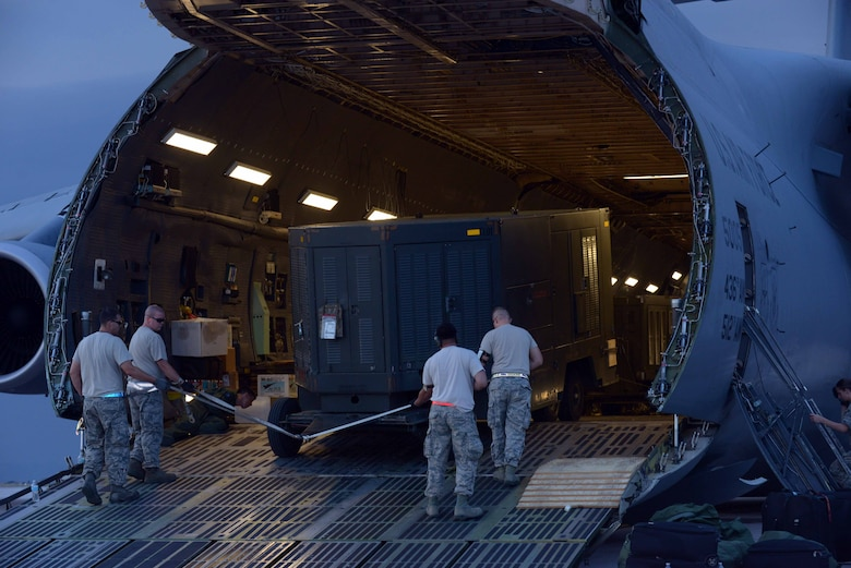 Airmen with the 28th Aircraft Maintenance Squadron guide equipment onto a Dover Air Force Base (AFB), Del., C-5 Galaxy at Ellsworth AFB, S.D., Aug. 2, 2016. The C-5 Galaxy is one of the largest aircraft in the world and has a greater capacity than any other airlifter, with the ability to carry 36 standard pallets and 81 troops simultaneously. (U.S. Air Force photo by Airman Donald Knechtel)
