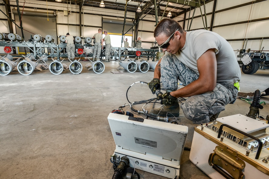 Senior Airman Cameron Kidd, 325th Maintenance Squadron, Tyndall Air Force Base, Fla., readies equipment for loading GPS data into GBU-32 bomb tail sections Aug. 2 at Hill AFB, Utah. The bombs will be dropped at the Utah Test and Training Range during the air-to-ground exercise known as Combat Hammer. Combat Hammer tests precision weapons for performance and suitability for combat. (U.S. Air Force photo by Paul Holcomb)