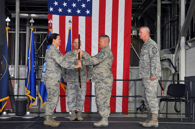 Col. Kristin Streukens, 151st Air Refueling Wing Commander, hands a musket to Chief Master Sgt. Matthew Hooper, 151st Air Refueling Wing Command Chief, during a transfer of responsibility ceremony on Aug. 7, 2016, at the Roland R. Wright Air National Guard Base in Salt Lake City. The musket, representing the historic minuteman roots of the National Guard, was passed from the Wing's outgoing command chief, Chief Master Sgt. Barry Vance to Hooper through Streukens. (U.S. Air National Guard photo by Staff Sgt. Annie Edwards)