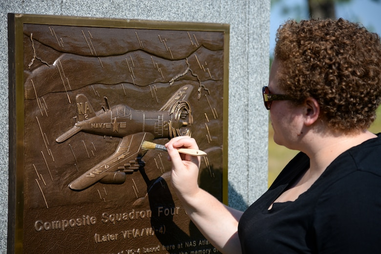 Melissa Swanson, Naval History and Heritage Command Conservator, applies a protective wax polish to a U.S. Navy VC-4 memorial marker, located near the main gate of the 177th Fighter Wing of the New Jersey Air National Guard in Egg Harbor Township, N.J., on July 21, 2016. The monument, erected in May 1994 by the Association of The Composite Squadron Four Nightcappers, pays tribute to the members of the VC-4 Squadron based at Naval Air Station Atlantic City from September 1948 to May 1958 who gave the ultimate sacrifice. Swanson, based out of Richmond, Virginia, earned an undergraduate degree in art history and anthropology from Wheaton College in Norton, Massachusetts and graduated from Columbia University in New York with a Master's of Science in Historic Preservation, with a specialty in materials conservation, focusing on working on metals, woods and stone. (U.S. Air National Guard photo by Master Sgt. Andrew J. Moseley/ Released)