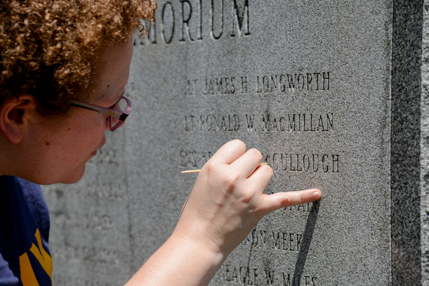 Melissa Swanson, Naval History and Heritage Command Conservator, uses a wooden pick to remove lichens growing inside the letters of inscriptions on a U.S. Navy VC-4 memorial marker, located near the main gate of the 177th Fighter Wing of the New Jersey Air National Guard in Egg Harbor Township, N.J., on July 20, 2016. The monument, erected in May 1994 by the Association of The Composite Squadron Four Nightcappers, pays tribute to the members of the VC-4 Squadron based at Naval Air Station Atlantic City from September 1948 to May 1958 who gave the ultimate sacrifice. Swanson, based out of Richmond, earned an undergraduate degree in art history and anthropology from Wheaton College in Norton, Massachusetts and graduated from Columbia Univeristy in New York with a Master's of Science in Historic Preservation, with a specialty in materials conservation, focusing on working on metals, woods and stone. (U.S. Air National Guard photo by Master Sgt. Andrew J. Moseley/ Released)
