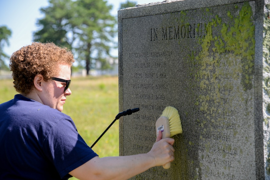 Melissa Swanson, Naval History and Heritage Command Conservator, uses a scrub brush to remove lichens growing on a U.S. Navy VC-4 memorial marker, located near the main gate of the 177th Fighter Wing of the New Jersey Air National Guard in Egg Harbor Township, N.J., on July 20, 2016. The monument, erected in May 1994 by the Association of The Composite Squadron Four Nightcappers, pays tribute to the members of the VC-4 Squadron based at Naval Air Station Atlantic City from September 1948 to May 1958 who gave the ultimate sacrifice. Swanson, based out of Richmond, Virginia, earned an undergraduate degree in art history and anthropology from Wheaton College in Norton, Massachusetts and graduated from Columbia University in New York with a Master's of Science in Historic Preservation, with a specialty in materials conservation, focusing on working on metals, woods and stone. (U.S. Air National Guard photo by Master Sgt. Andrew J. Moseley/ Released)