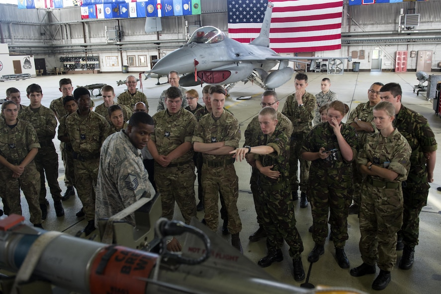 U.S. Air Force Master Sgt. Mandingo Alfred, 52nd Maintenance Squadron weapons superintendent, center left, answers questions from Royal Air Force Air Cadets during a tour at Hangar One on Spangdahlem Air Base, Germany, Aug. 9, 2016. Air Cadets, a United Kingdom-wide cadet force with more than 40,000 members aged between 12 and 20 years old, received an in-depth tour of 52nd Fighter Wing assets including the base fire department and an F-16 Fighting Falcon fighter aircraft. (U.S. Air Force photo by Airman 1st Class Preston Cherry/Released)