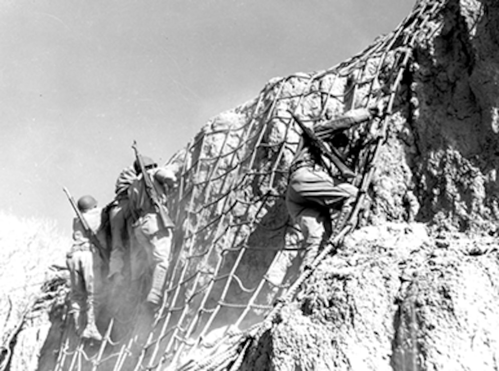 Troops from Fort Huachuca scale cargo nets and assault the ghost town of Charleston, Arizona, to practice house-to-house fighting. Source: Fort Huachuca Military Museum.