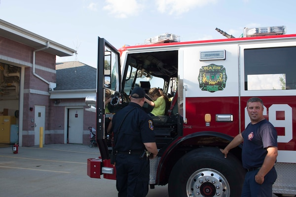 A DLA police officer helps a child explore a fire truck at Defense Distribution Center Susquehanna's National Night Out.