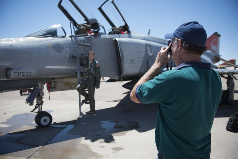 Retired Col. David takes a photo of his daughter, Cadet 2nd Class Kaitlyn, standing next to an F-4 Phantom on July 12, 2016 at Holloman Air Force Base, N.M. David came to surprise his daughter, a junior at the Air Force Academy, after her first flight in a fighter jet with the 96th Test Group Detachment 1. (Last names are being withheld due to operational requirements. U.S. Air Force photo by Airman 1st Class Randahl J. Jenson)