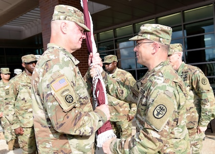 Col. (Dr.) Shawn Nessen (left) takes the U.S. Army Institute of Surgical Research flag from Maj. Gen. Brian Lein, commanding general of U.S. Army Medical Research and Materiel Command and Fort Detrick, Md., July 19.