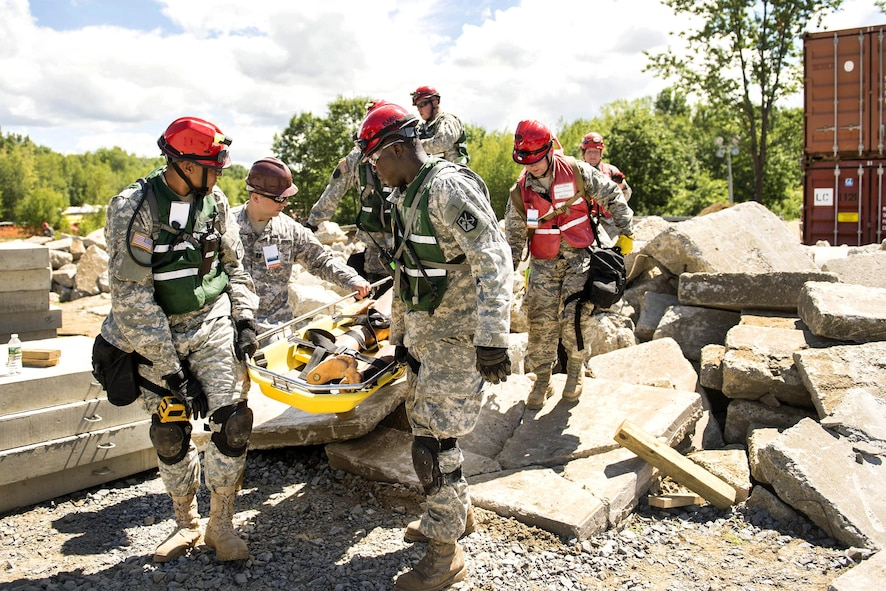 Guardsmen carry a stretcher with a simulated casualty.