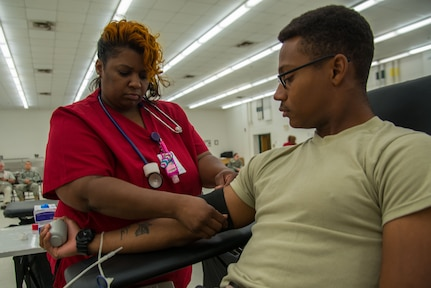 Felicia Taylor, American Red Cross phlebotomist collection technician three, prepares Spc. Curtis Smith, 335th Transportation Detachment watercraft operator, to donate blood during a blood drive at Fort Eustis, Va., August 3, 2016. Whole blood donation is the most common type, during which approximately a pint of whole blood is given. (U.S. Air Force photo by Staff Sgt. J.D. Strong II)