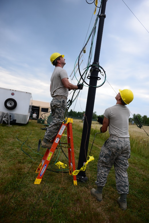 From the left, Senior Airman Robert Bell, and Senior Airman Matthew Barricklow, both from the 157th Communications Flight, adjust the height of a radio communication antenna during a training exercise at the New Hampshire Air National Guard Training Site in Center Stratford, N.H., Aug. 6. The antenna was part of the Joint Incident Site Communications Capability (JISCC) that was used to execute the exercise in support of domestic operations. (Air National Guard photo by Senior Airmen Kayla McWalter)