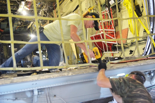 Kelly Kim, 560th Software Maintenance Squadron aircraft mechanic, replaces floor panels on an Air Force Special Operations Command MC-130H Combat Talon. (U.S. Air Force photo by Ray Crayton)