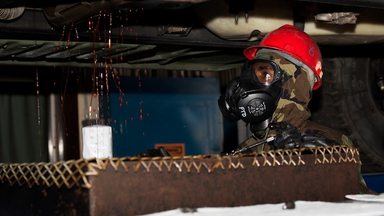 """U.S. Marine Corps Sgt. Lamarcus Williams, motor transportation mechanic and quality control chief with Combat Logistics Company 36, drains the transmission fluid from a high mobility multipurpose wheeled vehicle during chemical, biological, radiological and nuclear defense training at Marine Corps Air Station Iwakuni, Japan, August 10, 2016. Marines, already in mission oriented protective posture gear, were evaluated on their ability to effectively detect, report, respond and operate in a simulated CBRN environment. When given the signal """"gas, gas, gas,"""" Marines scrambled to don their M50 Joint Service General Purpose Masks before returning to work as if everything was normal."""