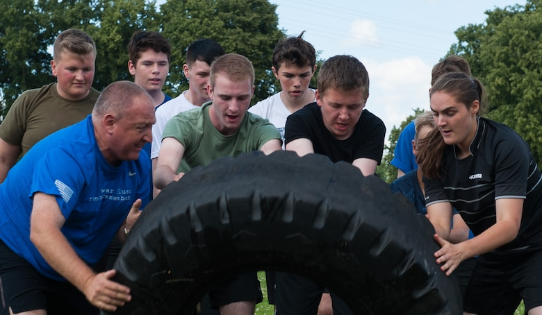 Royal Air Force cadets flip a tire during Warrior Day, a physical regimen hosted by the Kisling NCO Academy Aug. 8, at Vogelweh Military Complex, Germany.  Warrior Day is an annual mentorship program between the Air Force and the United Kingdom, where NCOA cadre provide insight on how Airmen train and stay educated. This event serves as a way for the U.S. continues to strengthen its relationship with the U.K. by showing the air cadets how the Kaiserslautern Military Community works together and through physical exercises. (U.S. Air force photo/Airman 1st Class Lane T. Plummer)