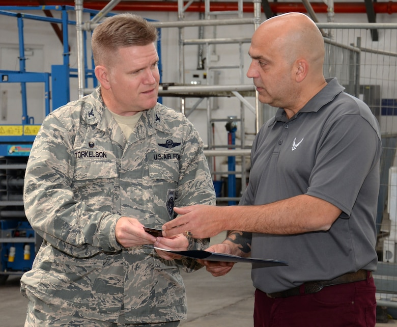 Steven Randall, right, 100th Logistics Readiness Squadron distribution manager, receives a pin for 30 years of service to the U.S. government from U.S. Air Force Col. Thomas Torkelson, 100th Air Refueling Wing commander, Aug. 10, 2016, on RAF Mildenhall, England. Randall began employment on RAF Mildenhall in 1996 after working at RAF Lakenheath for 10 years, and currently runs the cargo movement and vehicle operations elements for the squadron. (U.S. Air Force photo by Gina Randall)
