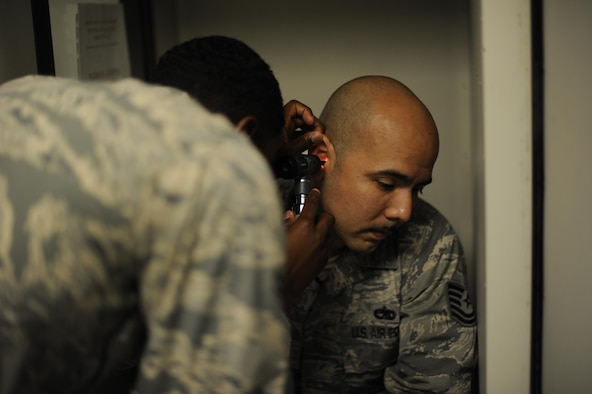 Airman 1st Class Kevin B. Baker checks Tech. Sgt. Daniel Cavazos' ears for blockage prior to an audiogram (hearing test) at the 87th Medical Group on Joint Base McGuire-Dix-Lakehurst, N.J., Aug. 10, 2016. Public Health stepped up to help out night shift aircraft maintainers and ensure preventative medical care is available to them. Baker is an 87th Aerospace Medicine Squadron public health technician and Cavazos is a 305th Aircraft Maintenance Squadron flight line expeditor.