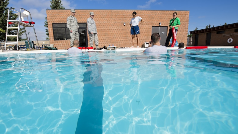 Airmen from the 5th Medical Operations Squadron prepare to practice their water extraction skills during training at the base pool at Minot Air Force Base, N.D., Aug. 10, 2016. The water extraction training involved performing emergency medicine on a simulated patient in a water environment. (U.S. Air Force photo/Airman 1st Class J.T. Armstrong)