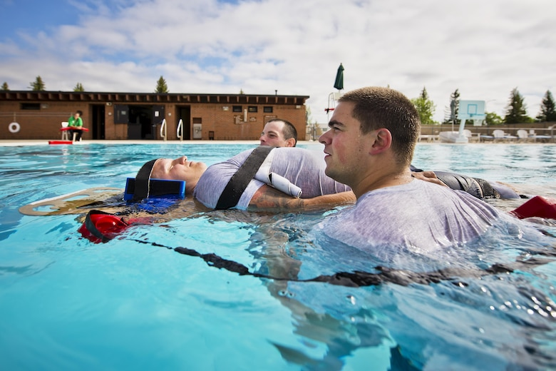 Airmen from the 5th Medical Operations Squadron move a simulated patient during training at the base pool at Minot Air Force Base, N.D., Aug. 10, 2016. A water rescue board is used in conjunction with lifeguard buoys to keep the patient above water during the rescue. (U.S. Air Force photo/Airman 1st Class J.T. Armstrong)